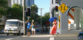 Woman with blue parasol at intersection.png
