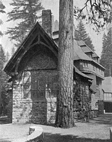 A monochrome photograph of the exterior of a building made of river rock, showing tall stained glass windows at one end, next to the massive trunk of a tall pine tree.
