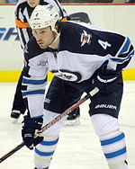 A Caucasian hockey player. He is wearing a white jersey with blue shoulders with a jet over a maple leaf inside of a circle for the logo. He is bent over at the waist leaning on his stick.