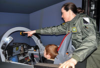110204-F-5560C-032 Lt. Sara Ferrero, Alabama ANG's first female F-16 fighter pilot shows a son the Fighter Fundamentals simulator.JPG