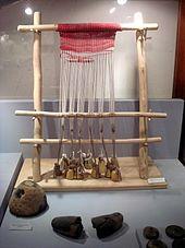 Photographie d'un métier à tisser vertical à pesons et à une barre de lisses, exposé dans la vitrine d'un musée.