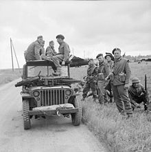 A black-and-white photograph of a jeep with soldiers sitting on top and standing beside it. The soldiers sitting on the jeep are three German soldiers and one British soldier who is interrogating the Germans. On the bonnet of the jeep is small motorcycle, while in the background is a Horsa glider