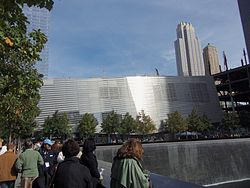 Silver-colored building, with square waterfall in foreground and skyscrapers in background