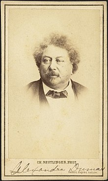 "Photograph of Alexandre Dumas wearing a bowtie and looking slightly off camera. A typed caption at the bottom of the image reads ""Ch. Reutlinger Phot."" and an annotation in pencil denotes the name of the subject."