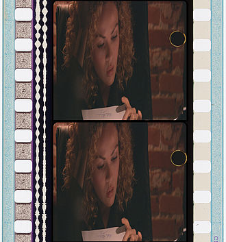 """Cue mark - This image demonstrates how a cue dot would appear on 35mm film. This is an anamorphic print with a (Westrex) """"stereo variable-area"""" sound track. An (analog) """"Dolby Stereo"""" track would be quite similar as a """"Dolby Stereo"""" track is an obvious application of a Westrex stereo variable-area track.."""