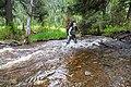 Backpacker crossing Little Cottonwood Creek (42457829671).jpg