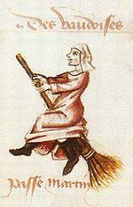 Desenul unei femei pe o mătură care pare să plutească în aer.  Poartă o coafură albă, o rochie roșie și cizme negre.