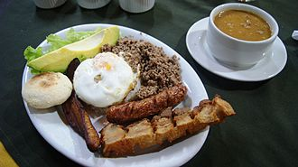 Colombian Americans -  A traditional Bandeja paisa meal. A staple dish assembled with several foods making necessary to use a platter. It is made of beans, rice, fried eggs, chorizo, pork rind and other ingredients depending on the location.