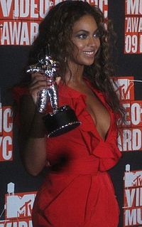 Knowles smiling and holding a Moonman statue