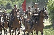 Kolorowa fotografia przedstawia grupę żołnierzy jadących konno, w różnych mundurach i z rozmaitym oporządzeniem. Na pierwszym planie widoczna grupa składająca się z oficera, podoficera w budionnówce na głowie z wyciągniętą szablą, za nimi widoczny żołnierz trzymający czerwony sztandar. W tle kolejnych kilku jeźdźców.