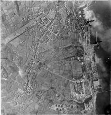 Vertical aerial photograph taken during a daylight attack on German warships docked at Brest, France. Two Handley Page Halifaxes of No. 35 Squadron RAF (upper right) fly over the naval dockyard, towards the dry docks in which the battlecruisers Scharnhorst and Gneisenau are berthed (top right) and over which a smoke screen is rapidly spreading. At middle right, a stick of bombs can be seen to have exploded inland from their intended target, Prinz Eugen, moored by the quayside. 47 aircraft from 3, 4 and 5 Groups took part in the operation, claiming accurate bombing on their targets for the loss of six aircraft