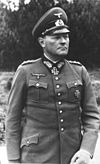 A man wearing a military uniform, peaked cap, e an Iron Cross displayed at the front of his uniform collar.