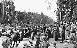 Photo noir et blanc prise le 5 octobre 1939, à Varsovie, en Pologne. Elle montre un défilé militaire de troupes de l'Armée allemande (à gauche) devant Adolf Hitler, debout et bras droit tendu devant lui, avec, dans son dos, une rangée d'officiers (à droite). Des arbres et un ciel clair forment l'arrière-plan de la photo.