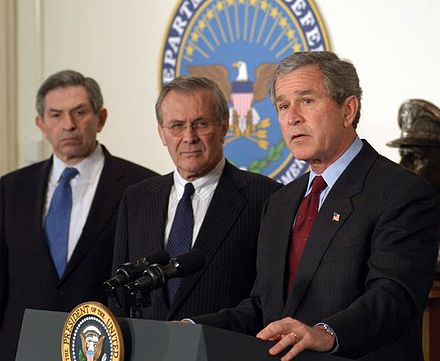 George W. Bush announces his $74.7 billion wartime supplemental budget request as Donald Rumsfeld and Paul Wolfowitz look on Bush War Budget 2003-crop.jpg