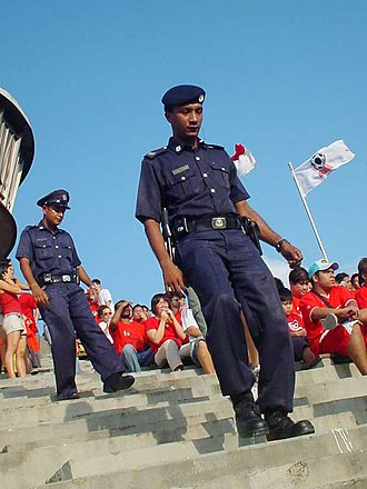 Certis Group - CISCO officers securing the National Stadium, Singapore just before the final match of the 2004 Tiger Cup. Two variants of the uniform may be seen, as seen in the different headdress and footwear, although both wore the short-sleeved version.
