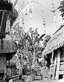 COLLECTIE TROPENMUSEUM 'De nieuwe padioogst is binnen de lumbungs versierd met pendjors lange gebogen bambu's versierd met slingers bossen padi en pluimen een vrouw is bezig met het stampen van padi in een blok Bali' TMnr 10011060.jpg