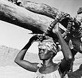 COLLECTIE TROPENMUSEUM Een vrouw vervoert via een draagstel hout op haar hoofd nabij To TMnr 20010513.jpg