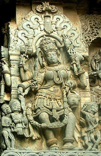 Matrikas - A Hoysala sculpture of Chamunda, Halebidu. Surrounded by skeletons, the goddess has large nails and protruding teeth and wears a garland of skulls.