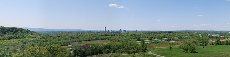 Panorama of the skyline of Albany, New York, taken from East Greenbush. The Empire State Plaza can be seen in the center and the northern end of the Catskill Mountains can be seen at far left. The Hudson River is in front of the Albany skyline and Interstate 90 can be seen in the foreground.