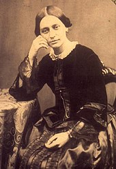 Black-and-white photograph of a woman sitting, looking pensively, with her left hand resting in her lap, while her head leans on her right hand, dressed in a solid-black jacket and lighter skirt