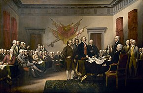 About 50 men, most of them seated, are in a large meeting room. Most are focused on the five men standing in the center of the room. The tallest of the five is laying a document on a table.