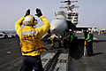 Defense.gov News Photo 110606-N-AV746-450 - Petty Officer 3rd Class Patrick Wight signals to the pilots of an F A-18 aircraft before launching off the flight deck of the aircraft carrier USS.jpg