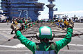 Defense.gov News Photo 110702-N-AW206-007 - U.S. Navy Petty Officer 3rd Class Ashley Pryor signals for sailors to set up the aircraft barricade during a barricade drill aboard the aircraft.jpg