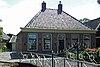 Boerderij met pannen schilddak, waarop hoekschoorstenen, voorgevel met houten kroonlijst en getoogde deur en vensters