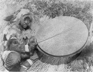 Yup'ik dancing - Nunivak Cup'ig playing a very large drum in 1927 by Edward S Curtis.