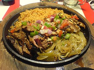 A mixed platter of beef and chicken fajitas wi...