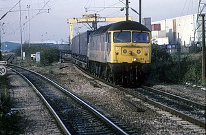 Dagenham Dock railway station - In October 1995, a Class 47 train departs Ripple Lane. The cranes of the depot can be seen in the background.