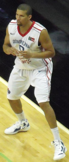 A man with a close-cut hairstyle, wearing a white basketball jersey, preparing to catch a pass