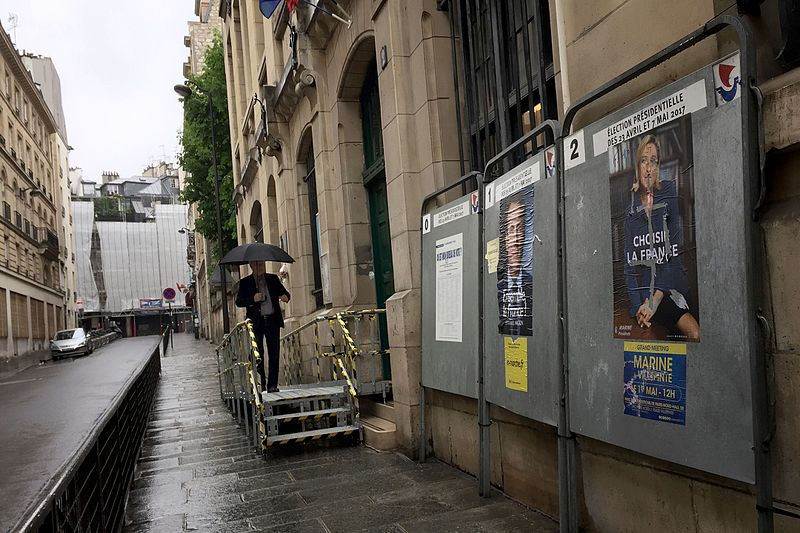 File:French Election, a poll worker arrives to a polling station in Paris in a light rain.jpg