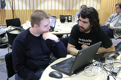 Two attendees sit behind a laptop at GLAMcamp London.