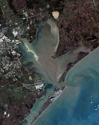 Galveston Bay - Satellite image of Galveston Bay. Galveston Island is at the bottom of the image, separated from Bolivar Peninsula by Bolivar Roads. A portion of Greater Houston is visible to the left.