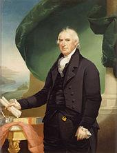 Un homme aux cheveux vaporeux blanc vêtu d'un costume noir et tenant une pièce enroulée de papier