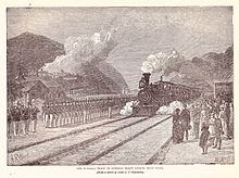 Drawing of a steam engine and train approaching station with an honor guard at attention