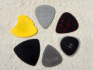 "Guitar pick - Various guitar picks. Clockwise from top: A standard nylon pick; An imitation tortoise-shell pick; A plastic pick with high friction coating (black areas); A stainless steel pick; A pick approximating a Reuleaux triangle; and a Tortex ""shark's fin"" pick"