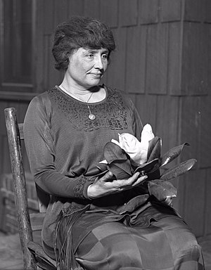 A woman with full dark hair and wearing a long dark dress, her face  in the partial profile, sits in a simple wooden chair. A locket hangs from a slender chain around her neck; in her hands is a magnolia, its large white flower surrounded by dark leaves.