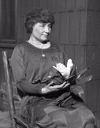 Helen Keller - Helen Keller holding a magnolia, ca. 1920.