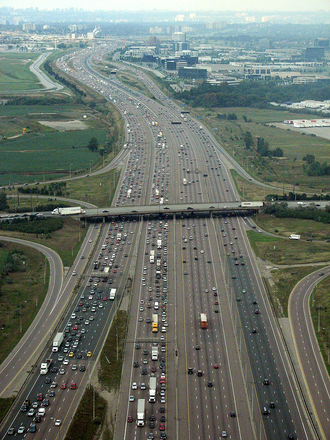 Suburbanization - Sprawling Freeway near Toronto, Canada with a suburbanized industry area in the background. Note the far distances from office buildings compared to a downtown. Many office buildings in suburban industry areas are set up on large irrigated campus, versus downtowns that have close buildings and very little greenery.