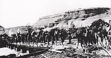 Many fully loaded camels crossing bridge built on square end boats; steep sided mountains in background