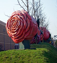 A large metallic sculpture of a red rose on a small grassy mound, with bare trees and other similar sculptures in the background