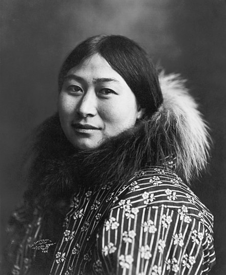 Photograph of Nowadluk/Nowadlook (Nora) Ootenna wearing a parka with a fur-lined hood, c. 1907. Ootenna was an Inupiat woman. Inuit Woman 1907 Crisco edit 2.jpg