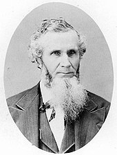 Formal portrait showing the head and shoulders of a white-haired, full-bearded man wearing a dark suit
