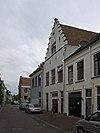 foto van Huis met gepleisterde en door pilaster op kraagsteensierankers bekroonde trapgevel