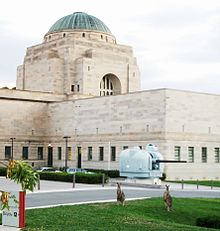 Kangaroos standing before naval gun turret. The domed structure in the background is the Hall of Memory.