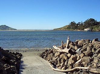Karitane - Waikouaiti River estuary at Karitane; fishing wharf and channel to the Pacific Ocean at right, Matanaka headland at left background.