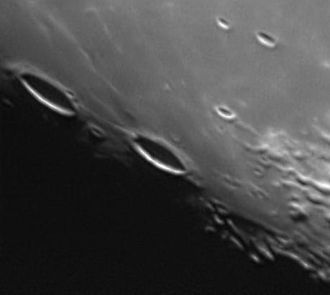 Cardanus (crater) - Cardanus (center) and Krafft (left) near the terminator, as viewed from Earth. Also visible is the Rima Cardanus between them and the crater Galilaei beyond.