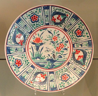Japanese export porcelain - Large Export Dish, c. 1660–1670, Arita ware, hard-paste porcelain with overglaze enamels, the decoration drawing on Kraak ware Chinese export porcelain, though this is normally in blue and white.